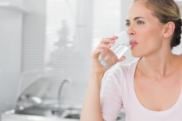 Pensive blond woman drinking water