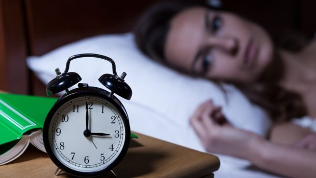 Alarm clock on night table showing 3 a.m.