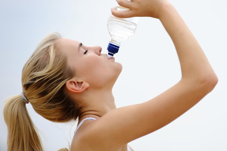 Blond girl drinks water